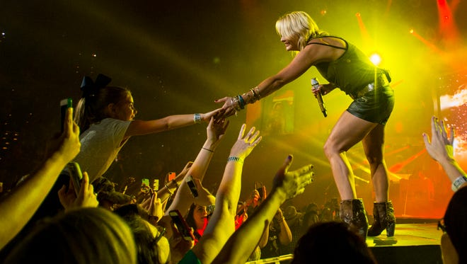 Country musician Miranda Lambert touches fans while performing on the Platinum Tour at the Cajundome in Lafayette, La., Friday, Sept. 12, 2014.