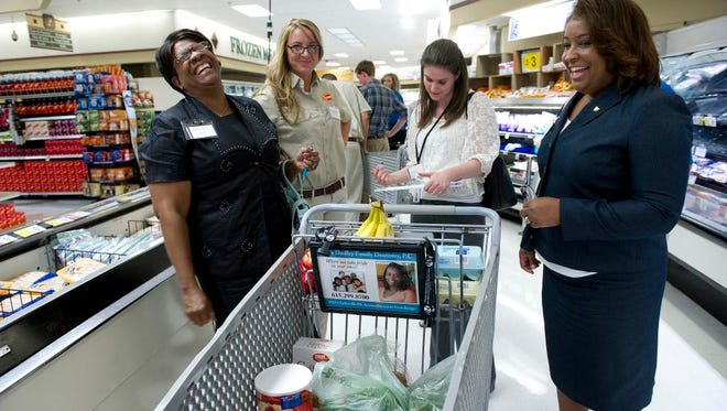 Minnie Mitchell, left, Anna Davenport, Allison Thigpen and LaTrisha Jemison participate Thursday in a challenge in which they buy food for a fake family of four using the equivalent of federal benefits.