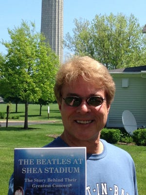 Author Dave Schwensen displays one of his Beatles books while visiting Put-in-Bay.