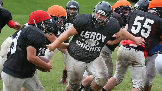 LeRoy defensive lineman Luke Hogle, center, sheds blockers as he breaks into the backfield in pursuit of the run during practice at LeRoy High School in this 2015 file photo.
