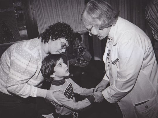Dr. Katherine Esterly greets 6-year-old William Scott and his mother, Carol, at a party for premies in 1985.