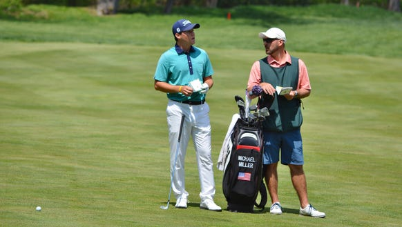 Mike Miller discusses yardage in the 18th fairway with