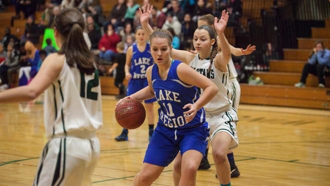 Lake Region's Megan Menard, center, posts up a Winooski defender on Tuesday night at Winooski High School.