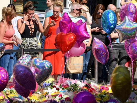 Members of the public look at tributes left for the