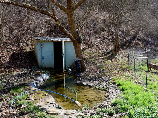Pipes run from  the springhouse behind David Cooke's trailer home in rural Madison County. Cooke, who did not have hot water for more than two years, also went for a time without running water at all.
