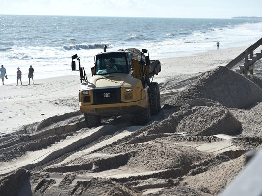 Workers from Mancil's Tractor Service, of Palm City, move tons of beach sand to replenish the dune at Conn Beach on Friday, Feb. 9, 2018, in Vero Beach. The City of Vero Beach hired Mancil's to place approximately 7,600 cubic yards of sand to rebuild the dune line along the boardwalk, which had heavy erosion caused by Hurricane Irma in September, 2017. The project is scheduled to be completed by the end of February