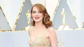 Lights! Cameras! Action!  Emma Stone is golden on the red carpet during the 89th Academy Awards at Dolby Theatre.