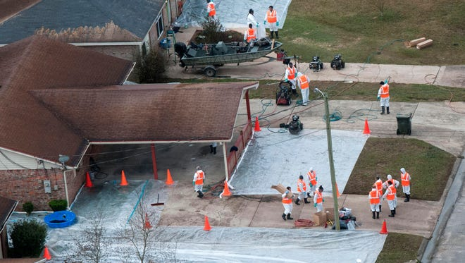 """Workers continue cleanup efforts in the Woodbury Circle area in the shadows of the International Paper plant in Cantonment Thursday morning. An explosion at the IP plant on Sunday coated the neighborhood with  """"black Liquor"""" fallout."""
