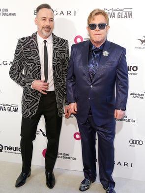 Elton John, right, with husband David Furnish, hosted