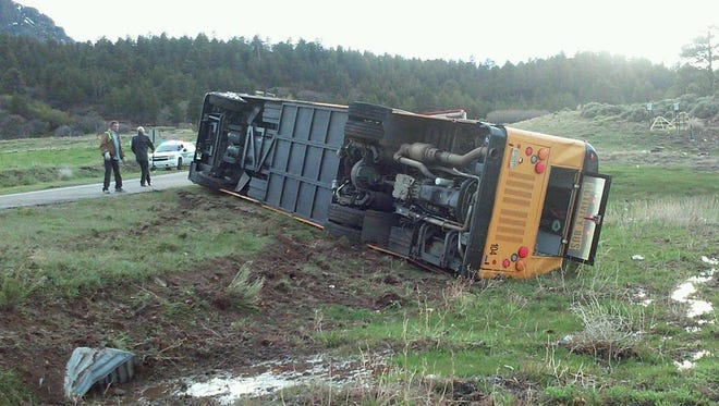 A Farmington Municipal School District bus rests on its side after a May 4, 2015, crash on Indian Route 13 near Red Valley, Ariz.