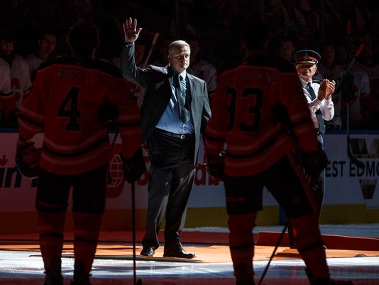 Edmonton police Constable Michael Chernyk waves to the crowd as he is honored before an NHL hockey game Wednesday, Oct. 4, 2017, in Edmonton, Alberta between the Calgary Flames and the Edmonton Oilers. Chernyk was injured in an attack when he was handling crowd control at a Canadian Football League game last week. (Jason Franson/The Canadian Press via AP)