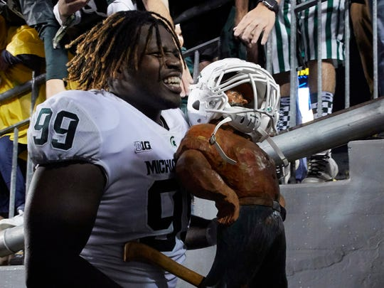 Michigan State Spartans defensive tackle Raequan Williams (99) carries the Paul Bunion trophy off the field after defeating the Michigan Wolverines at Michigan Stadium.