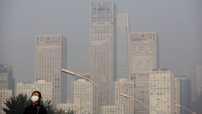 A woman wearing a mask to protect herself from pollutants stands on a pedestrian bridge as buildings at Beijing's Central Business District are shrouded in haze on Nov. 25, 2014.