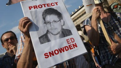 A participant holds up a picture of former NSA employee Edward Snowden at a protest in front of the Brandenburg Gate against the electronic surveillance tactics of the NSA on July 27, 2013, in Berlin.