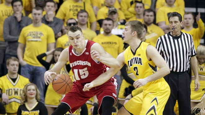 Iowa's Josh Oglesby, right, guards Wisconsin's Sam Dekker during the second half of an NCAA college basketball game Saturday, Jan. 31, 2015, in Iowa City, Iowa.
