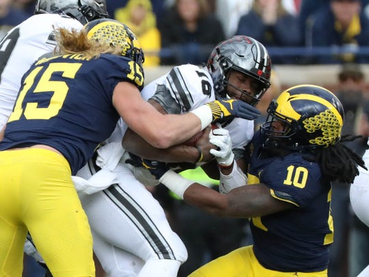 Michigan's Chase Winovich, left, and Devin Bush tackle Ohio State's J.T. Barrett in the first quarter Nov. 25.