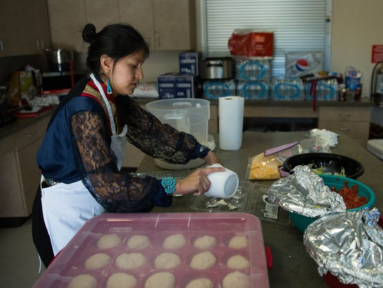 Desiree Lapahie mixes dough for Indian tacos in the