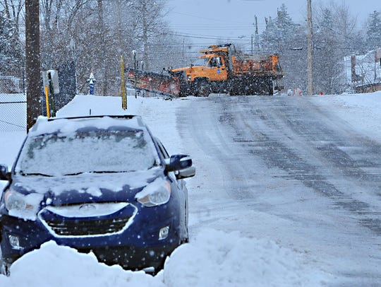 A snowplow clears Chambersburg streets Monday, March