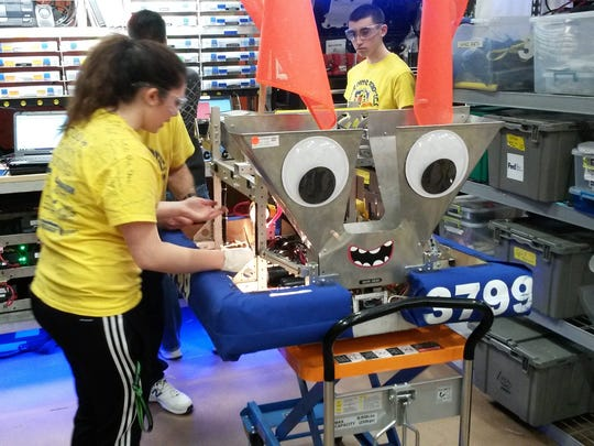 Members of Notre Dame's The Electric Fire robotics team assemble their robot prior to the regional competition in Rochester.