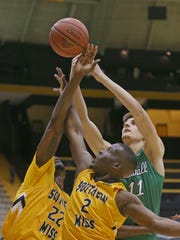 Marshall forward Ajdin Penava (11) battles Southern Miss guards Quinton Campbell (22) and D'Angelo Richardson (2) for a rebound Thursday at Reed Green Coliseum.