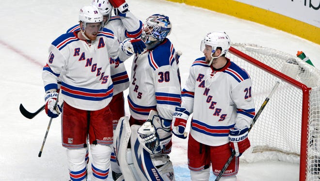 New York Rangers goalie Henrik Lundqvist (40 saves) celebrates the win over the Montreal Canadiens with teammates.