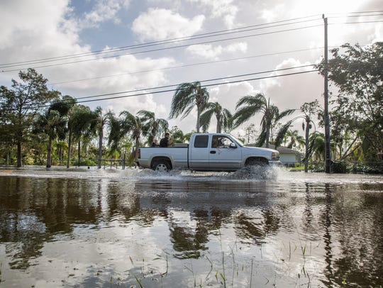 A car passes by on a road left flooded by Hurricane