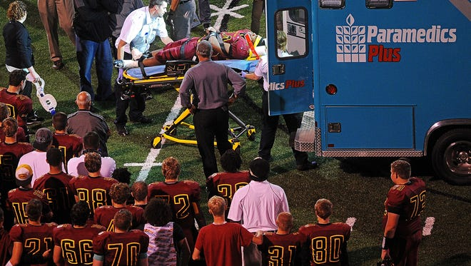 Surrounded by teammates and family, Roosevelt's Piercen Evans (44) is put into an ambulance after sustaining an injury during a game Friday, Sept. 25, 2015, at Howard Wood Field in Sioux Falls. Coach Kim Nelson said Evans will be alright.