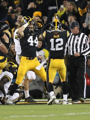 Iowa Hawkeyes linebacker Ben Niemann (44) and Iowa Hawkeyes defensive back Anthony Gair (12) signal for the safety against the Michigan Wolverines at Kinnick Stadium.