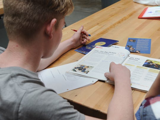 Samuel Vance, eighth-grader, searches for an answer to a worksheet question in a book about Future Farmers of America during an introduction to agriculture class Wednesday at Westfall High School.
