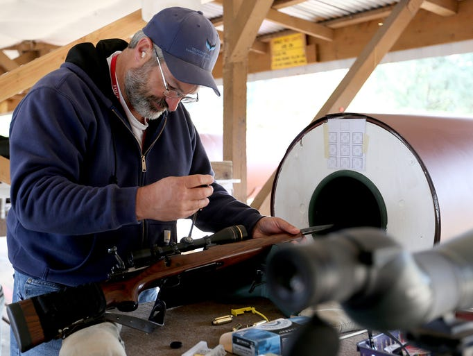 Chris Hottorf, a club member, adjusts a rifle scope