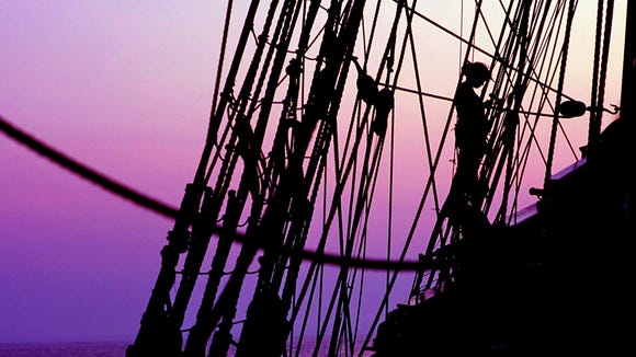 Dusk settles over the Kalmar Nyckel as a crew member continues her work.