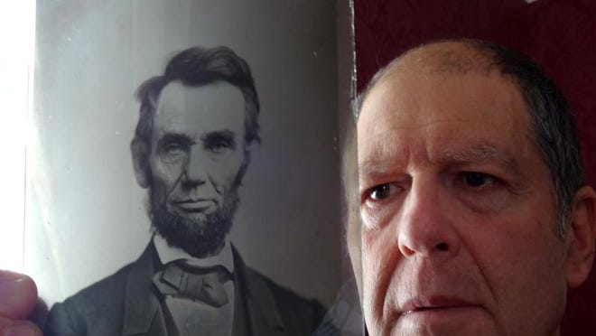 Paul Turner of Salisbury holds a glass  negative of President Abraham Lincoln owned and made by his great-grandfather Moses P. Rice. The original photo is believed to have been taken in the Washington studio of photographer Alexander Gardner.