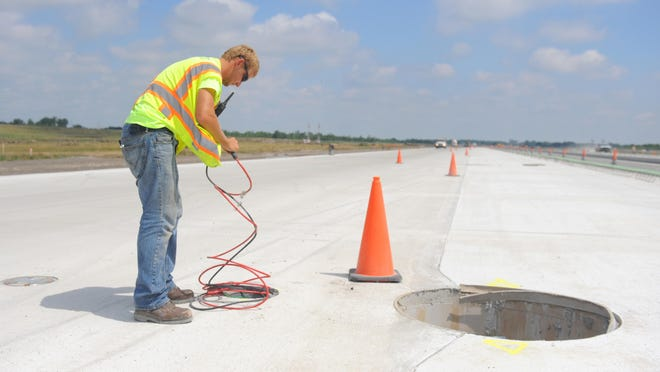 Detroit City FC midfielder/forward Tommy Catalano works on the the lighting for the new runway at the at Detroit Metro Airport.