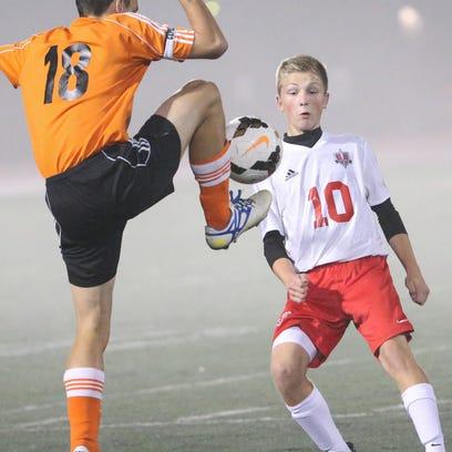 Ben Giese (18) of North Fond du Lac kicks the ball away from Dan Dunn (10) of Lourdes Academy.