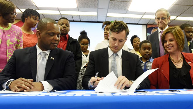 State Superintendent of Education John White, right, and Caddo Parish Schools Superintendent Lamar Goree sign papers regarding the announcement of a three-year agreement Wednesday to transform chronically failing schools in Caddo Parish.