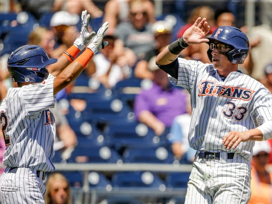 Cal State Fullerton's Hunter Cullen (33) celebrates with teammate Sahid Valenzuela (12) after he scored on a sacrifice fly by Scott Hurst in the third inning of an NCAA College World Series baseball game against Florida State, in Omaha, Neb., Monday, June 19, 2017. (AP Photo/Nati Harnik)