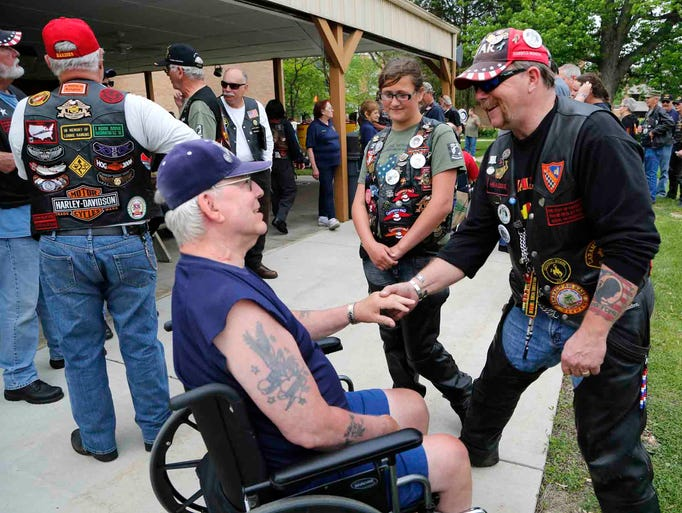 "Steve ""Headdog"" Moore and his granddaughter Sydney Kosek, 11, meet with Henry Stock as motorcyclists taking part in the National Veterans Awareness Ride stop Wednesday, May 21, 2014, to visit with the residents of Indiana Veterans' Home in West Lafayette. Moore presented Stock, an Army veteran of the Korean War and Vietnam War, with a commemorative pin from this years ride."