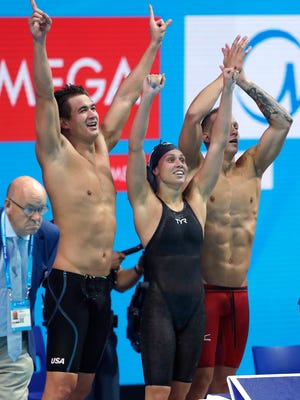 United States' Nathan Adrian, Mallory Comerford and Caeleb Dressel, from left, celebrate after winning the gold medal in the 4x100-meter freestyle mixed relay final Saturday at the World Championships in Hungary.