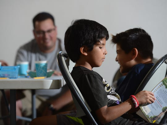 Bryce Phillips, back, an instructor, sits with Edwin Zavala, front, and Leonardo Cano during Project Safe Passage at an apartment complex on Warwick Avenue in Thousand Oaks.
