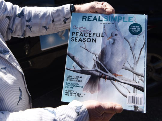 Charles Morgan displays an issue of Real Simple, which features one of his pigeons on the front cover.