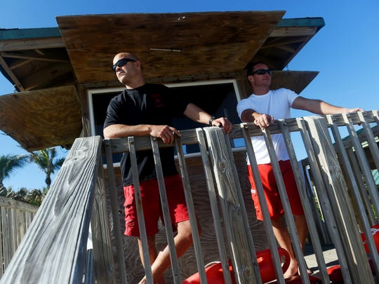 Indian River County lifeguards Johnathan Billings (left) and Michael Flinn stand watch Dec. 27, 2017, over Wabasso Beach from the lifeguard tower. Along with three other lifeguard friends, they form Red Buoy Brewers, a club of beer home brewers.