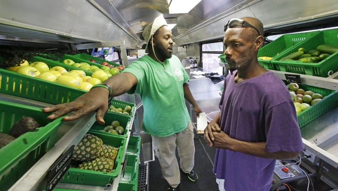 In this file photo, Fresh Stop employee Jamar Allen, left, helps Jock Riggins as he shops on the Fresh Stop bus, a mobile market, in Eatonville, Fla. The Fresh Stop brings fresh fruits and vegetables to communities with no supermarkets. The nation's largest grocery chains have built new supermarkets in only a fraction of the neighborhoods where they're needed most, according to an analysis of federal food stamp data by The Associated Press.