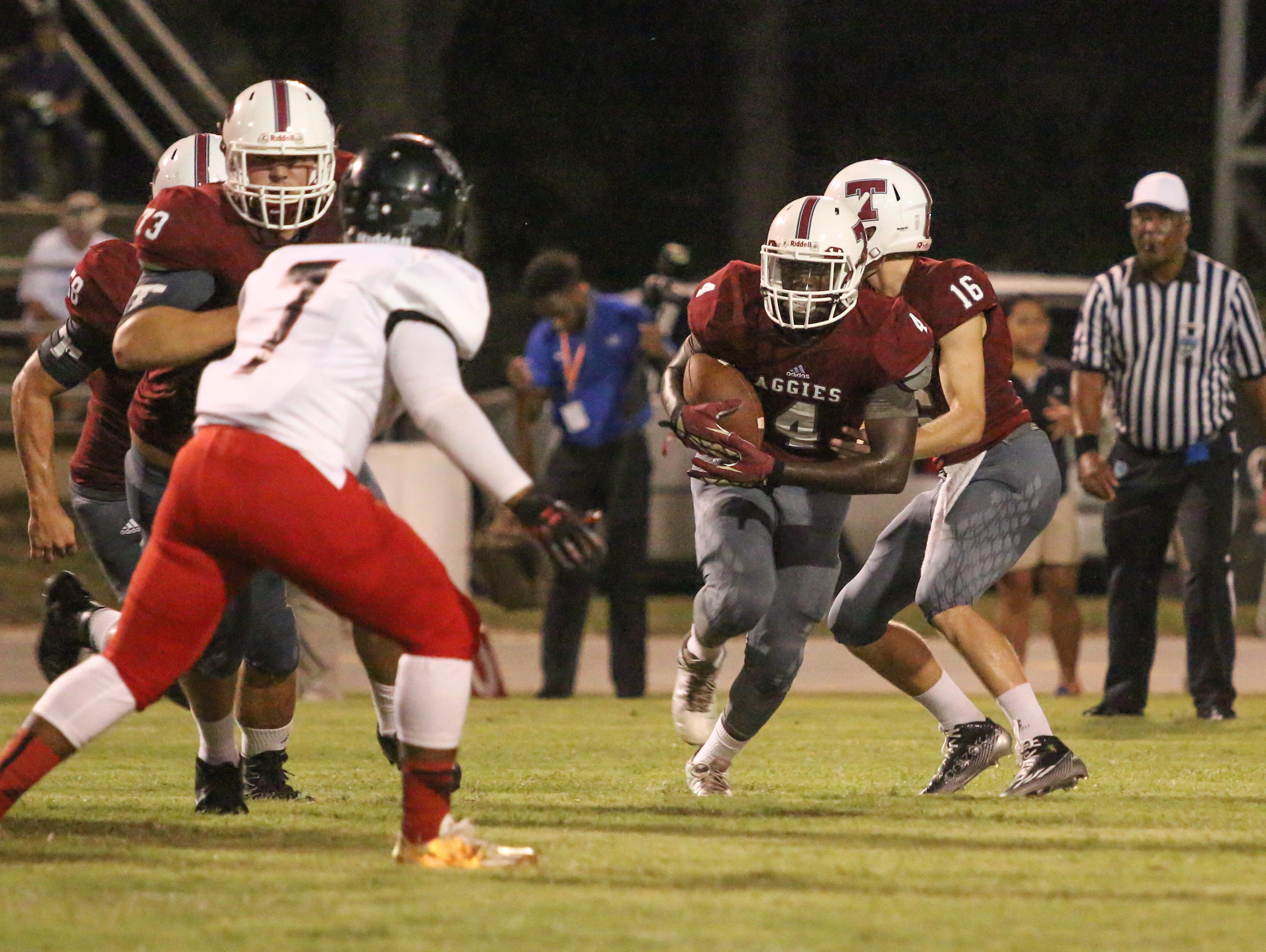 Tate's Ladarryl Paige (4) runs with his lead blocker, Tyler Dorsett (73), as West Florida's Corey Marioneaux (7) prepares to stop them Friday night at Tate High School.