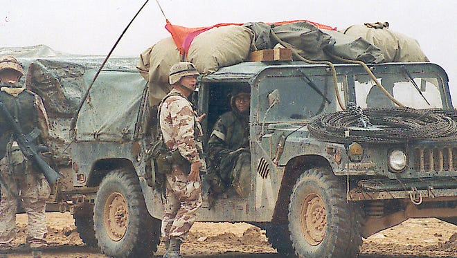 Command Sgt. Maj. Robert Nichols stands outside a Humvee during the Gulf War in 1991.