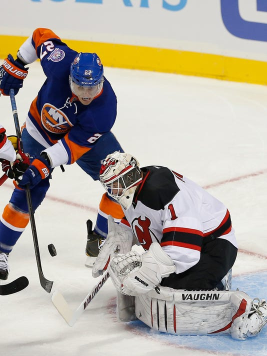 New Jersey Devils goalie Keith Kinkaid (1) makes a save on a shot by New York Islanders center Anders Lee (27) in the first period of a preseason NHL hockey game Friday, Sept. 26, 2014, in New York. (AP Photo/Paul Bereswill)
