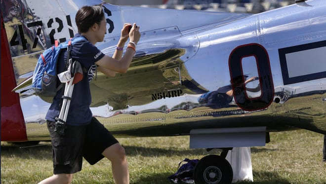 Jessie Kang, Maryland, takes a photo while touring the Warbirds of America Fightertown during AirVenture 2015 at Wittman Regional Airport on July 25, 2015 in Oshkosh, Wis.Wm.Glasheen/Post-Crescent Media