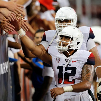 Arizona quarterback Anu Solomon (12) celebrates with fans after defeating California 49-45 on a game-winning Hail Mary twith no time on the clock on Saturday, Sept. 20, 2014, in Tucson.