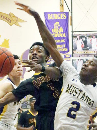 Shahodd Singleton, 3, of Andress runs into heavy traffic from Deion Bauman, 1, left, and Tristen Newton, 2, right of Burges Friday, Jan. 6 night at Burges. Singleton was fouled on the play.