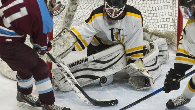 North Country's #11 Brady Perron gets up close and personal with a shot on Harwood Union goalie Sean Russell during the DII boys hockey state championship at UVM Thursday night, March 9, 2017. North Country won 4-3.