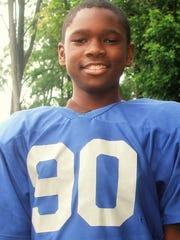 Isaiah Stuart as a young boy posing in his little league football uniform.